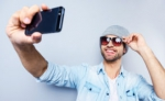 Selfie-Top-view-of-handsome-young-man-in-hat-and-sunglasses-making-selfie-and-smiling-while-standing-against-grey-background - Вечер Елабуги